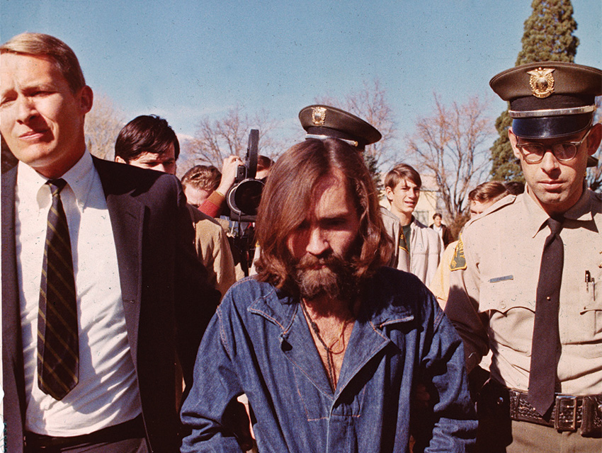 Officers escort Manson to jail following a preliminary court appearance in December 1969 in Los Angeles