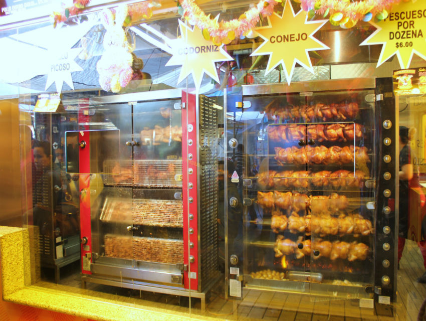 Whole chickens, rabbits, chicken necks, and quail on the rotisserie at Mama Gallina
