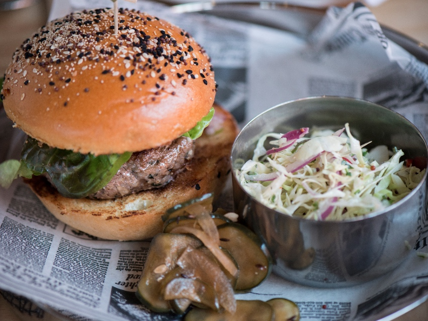 The Masala Lamb Burger is topped with tomato, red onion & cilantro relish, preserved tomato chutney