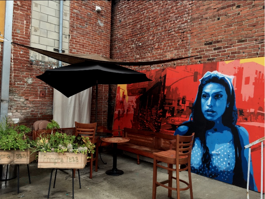 Primera Taza's Patio with a mural by Ray Vargas