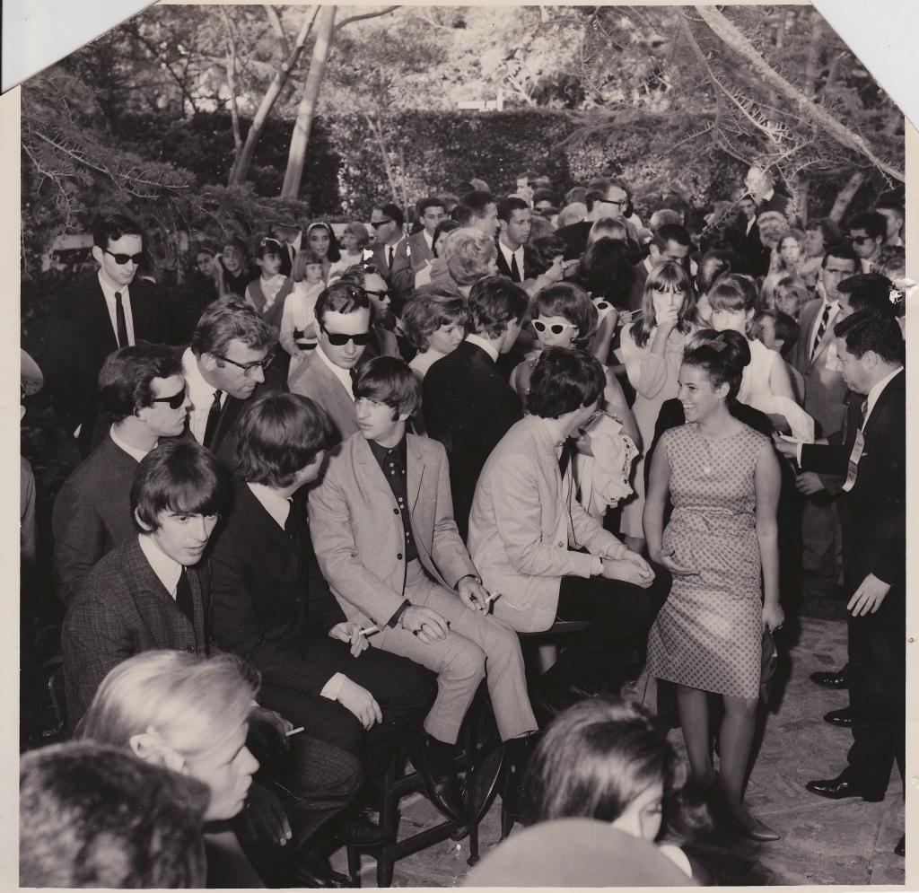 Road manager and personal assistant Mal Evans leans down to speak to Ringo Starr; road manager Neil Aspinall looks cool in shades standing next to band manager Brian Epstein; Bonnie Cowan Fleming speaks to Paul McCartney while her father, publicist Warren Cowan, greets everyone in line; Jayne Meadows stands behind McCartney.