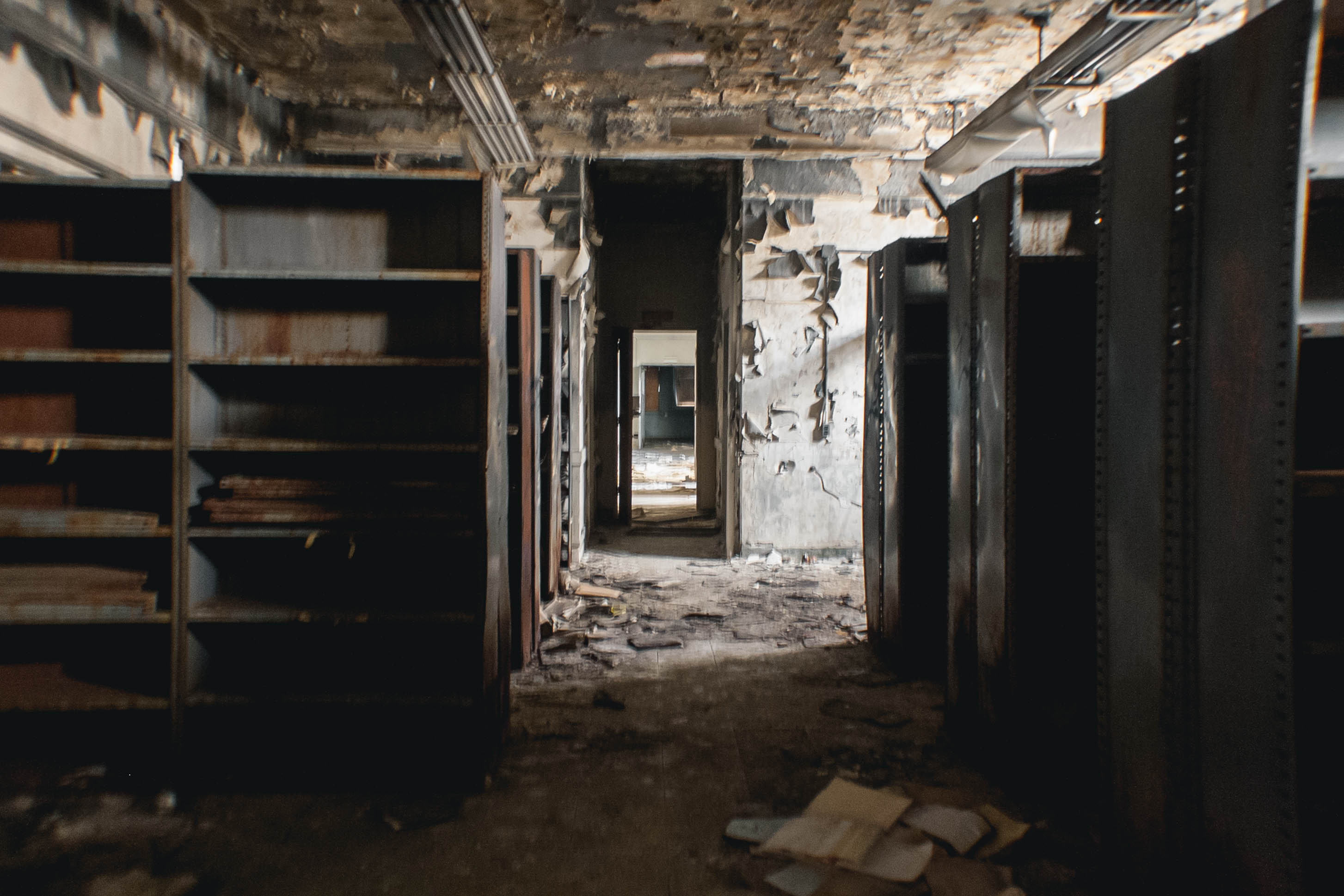 """This is inside the fire-damaged building. Walking around I could see damaged office equipment, paperwork, and books. Further in I found a room that was completely destroyed. There were books everywhere. All the windows were boarded shut and the floors and walls creaked with every step. I decided to leave because I was afraid the room would collapse."""