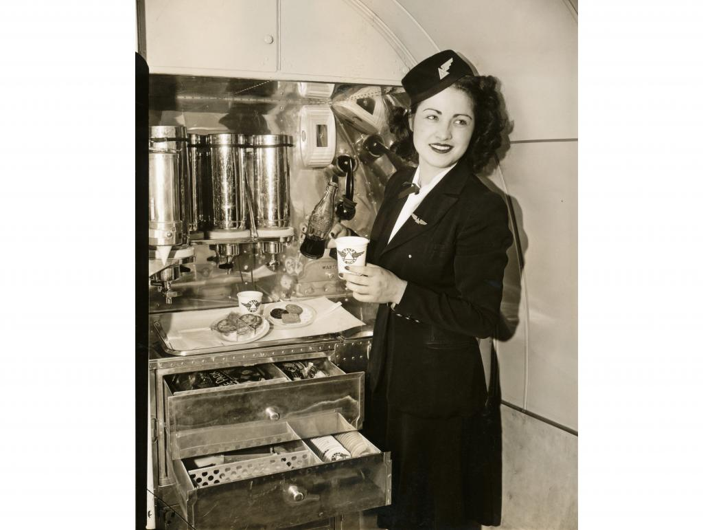 Delta stewardess pouring Coca-Cola into a paper cup in DC-3 galley. Snack plates with cheese, crackers and cookies on counter. Open drawers show supplies including an ice pack and more paper cups. The DC-3 was the first airplane with a planned food galley.
