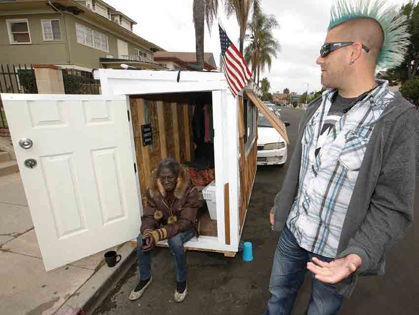 """Elvis Summers (right) welcomes Irene """"Smokie"""" McGhee to her new residence, one of many he built for the homeless in South L.A."""
