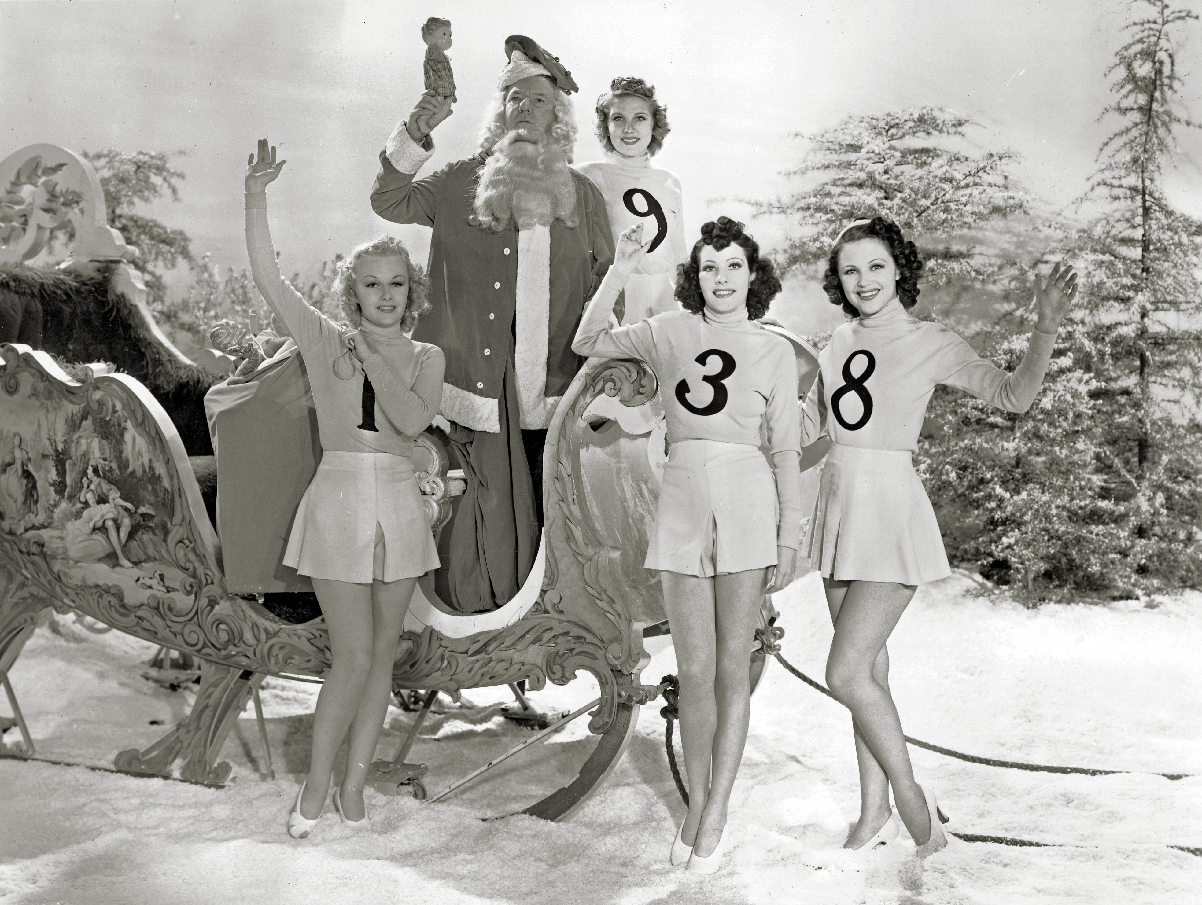 Comedian W.C. Fields dresses as Santa Claus and rings in 1938 in the company of some beautiful Paramount starlets.