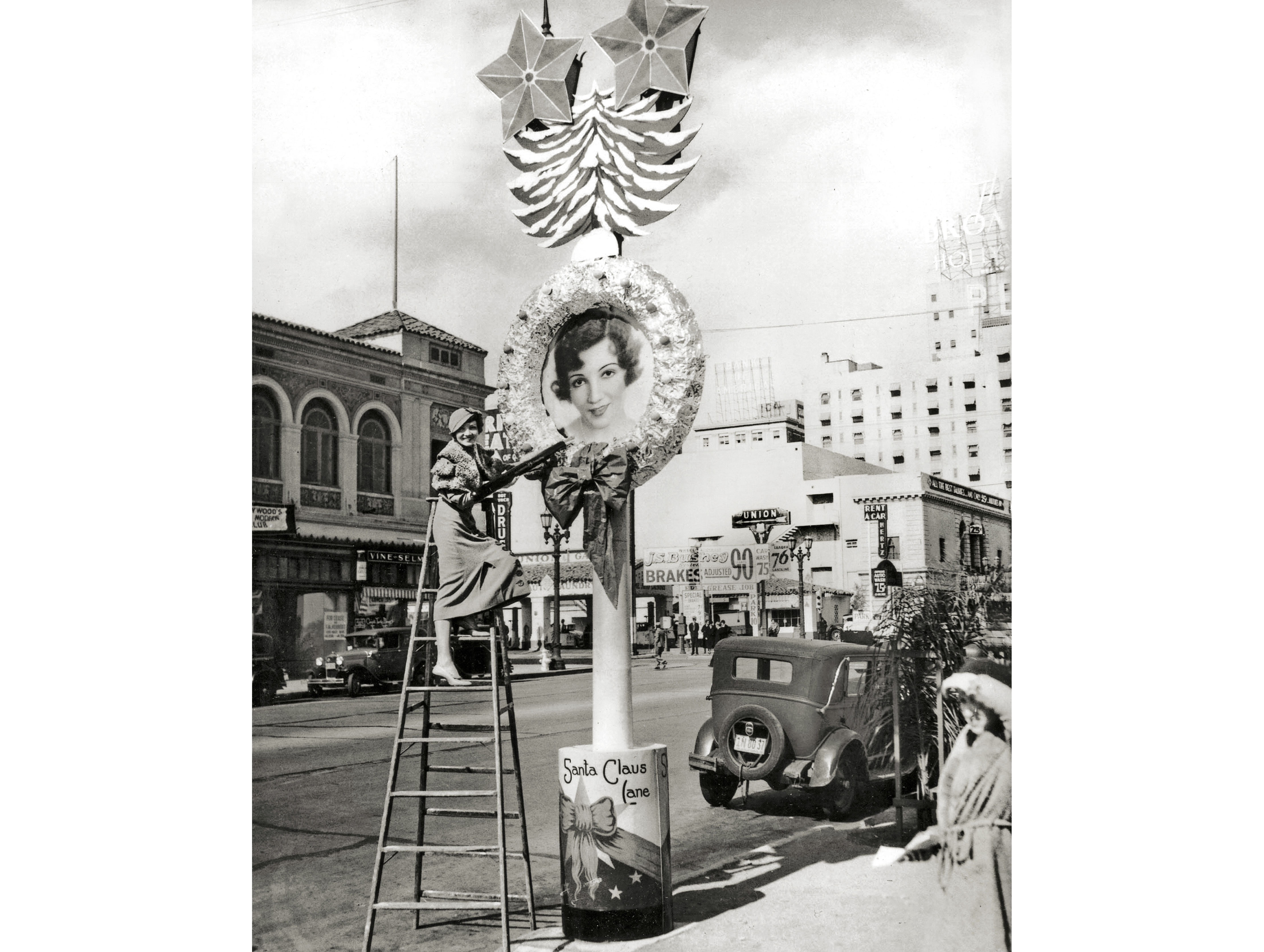Claudette Colbert admires her oversized portrait lining Vine Street in Hollywood for the 1932 Santa Claus Lane shopping season.