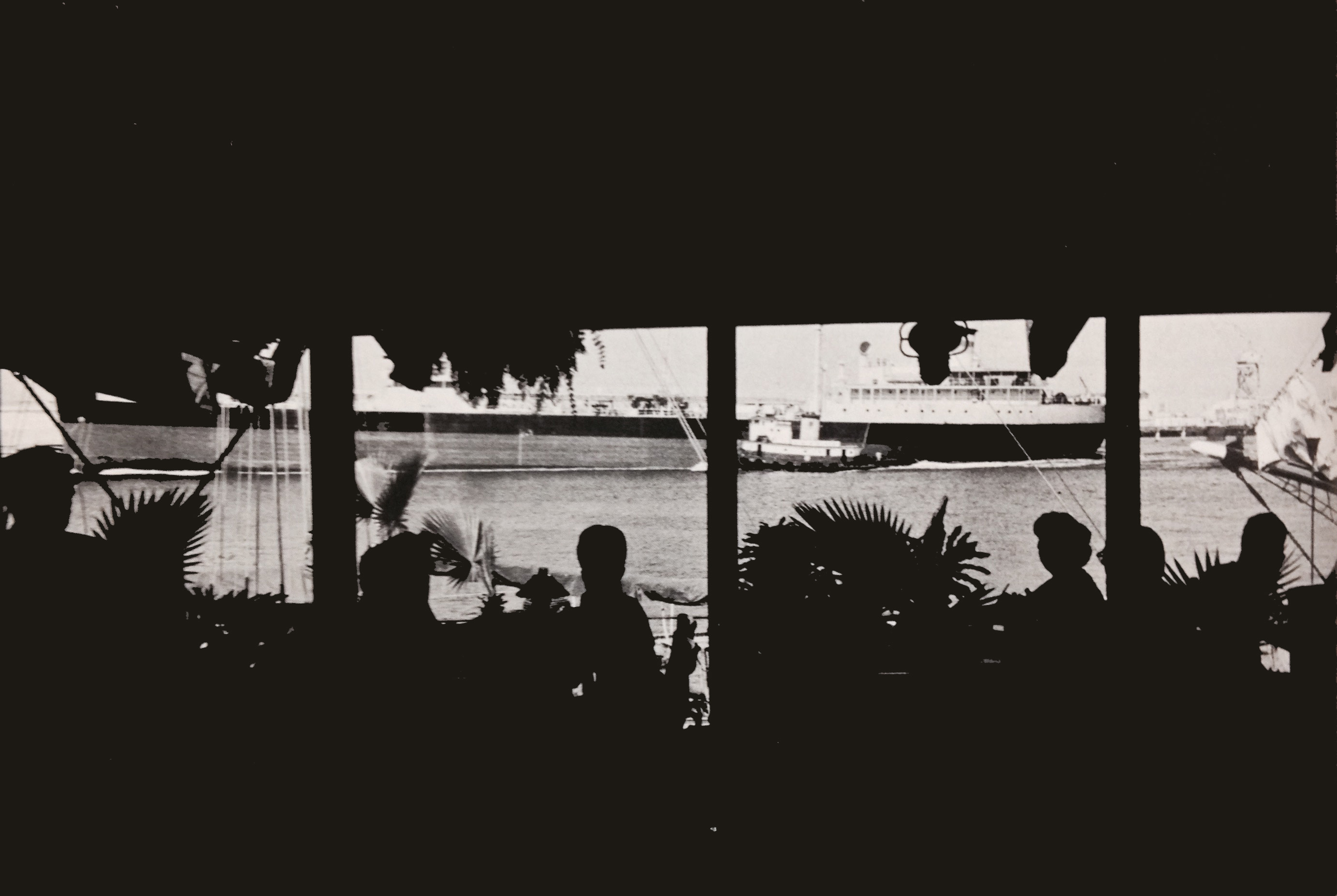 Diners in a waterfront restaurant watch outward-bound freighters and dream between courses of faraway places.