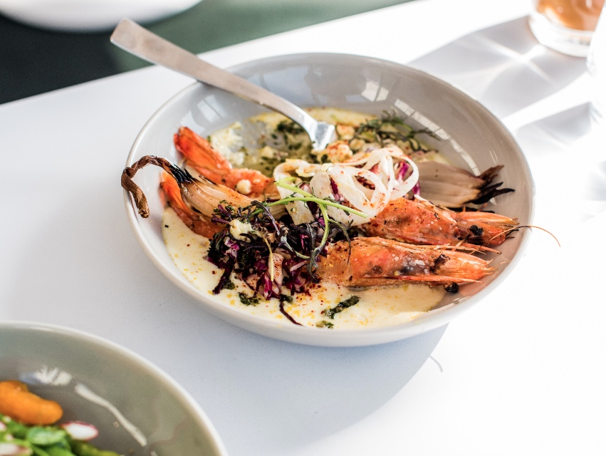 Prawns are served with whipped polenta, roasted shallot, and gremolata