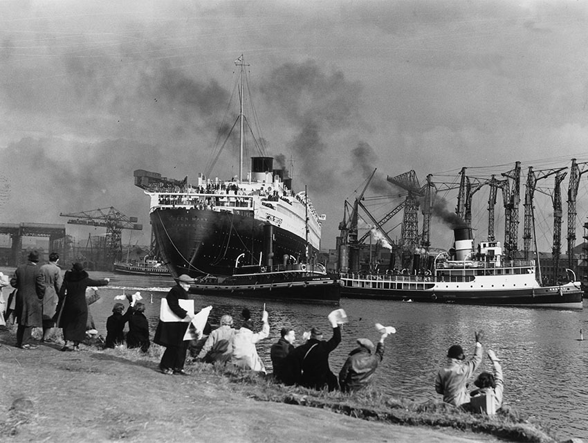 Crowds gather to watch the new Cunard White Star liner Queen Mary leaving her fitting-out berth in the John Brown & Co shipyard at Clydebank. Handkerchiefs are waved as the massive liner makes her way down the river Clyde to the sea, en route to Greenock and Southampton.