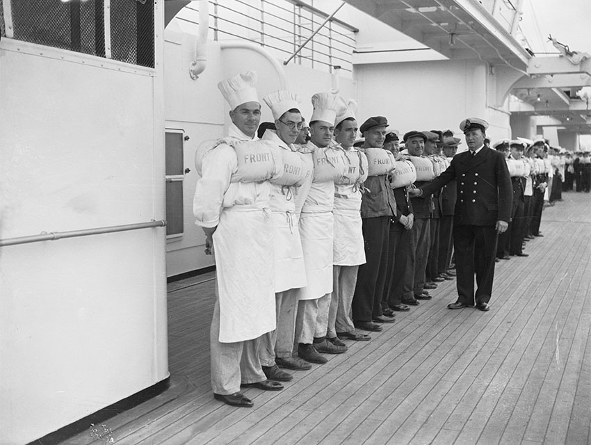 The crew of the Queen Mary line up on deck for a safety drill prior to the ship's departure on her maiden voyage from Southampton to New York.