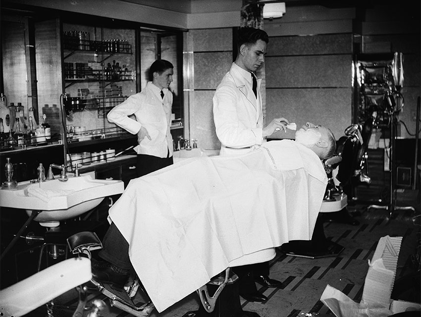 28th May 1936: A hairdresser at work on board the Queen Mary liner as it leaves Southampton on its maiden voyage to New York.