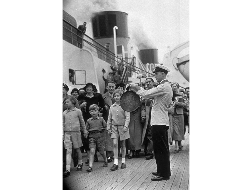 A steward 'gonging-off' visitors before the 'Queen Mary' left Southampton on her maiden voyage to New York.