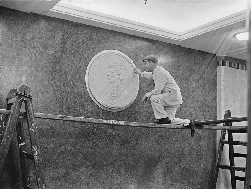 A workman putting the finishing touches to a plaque of the British Queen consort, Mary of Teck on the first class deck of the ocean liner RMS Queen Mary, during construction at the shipyard of John Brown & Company in Clydebank, Scotland, 3rd March 1936. The ship is almost ready for her maiden voyage on 27th May 1936.
