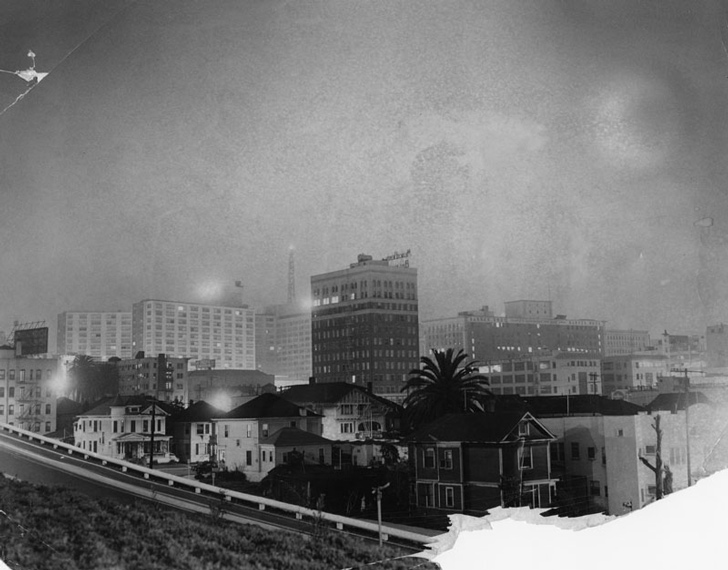 """""""A"""" bomb blast brightens L.A. at 5:20 a.m. as seen from the 9th Street cutoff of the Harbor freeway. Photograph dated March 12, 1955"""