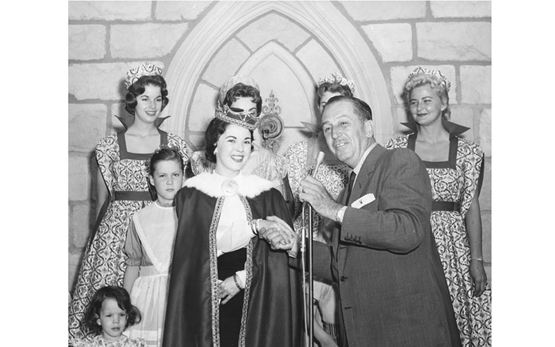 Shirley Temple told the story of Sleeping Beauty during the official opening of the interior of the Castle at Disneyland, Sunday, April 28, 1957. Left to right: Daughter, Lori, three; daughter, Susan, nine; Ms. Temple and Walt Disney. Disneyland ladies in waiting stand by to escort them through the castle interior.