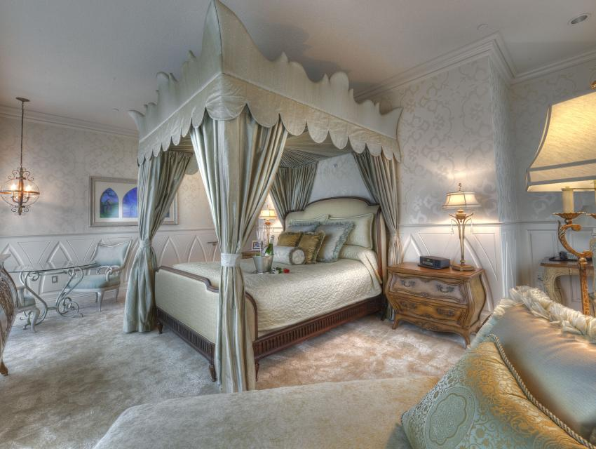 FAIRY TALE SUITE -- A marble foyer descends into an enormous bedroom overlooking the entire resort through floor-to-ceiling windows in the Fairy Tale Suite at the Disneyland Hotel. The sage and champagne colors used throughout the suite elegantly blend the combination of blonde and glass furniture and the suiteÕs centerpiece is an exquisite canopy bed overlooking the corner view. The room is finished with crown moulding, automatic drapes and a custom-designed dresser, from which a flat-panel television ascends at the touch of a button.