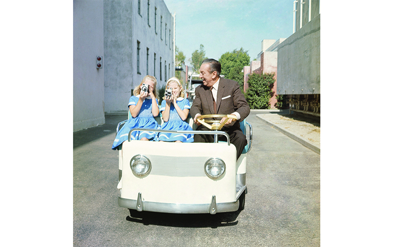 Walt Disney escorts two young visitors around the studio lot in 1962