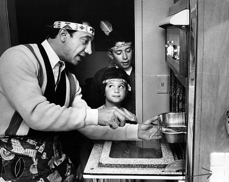 """Photograph caption dated November 23, 1964 reads, """"When the Sevens have Thanksgiving dinner the whole family gets into the act, especially when Daddy cooks. At left, Laura and Johnny sneak a peak into the oven. At right, Laura helps her mother stir batter for Johnny cakes. After Seven began studying about the Indians, the children became interested too. This, of course, called for feathers and headbands for everyone, including Georgie, the family dog. Mrs. Seven says that some of the research was a help to the children at school because history goes hand-in-hand with food."""""""