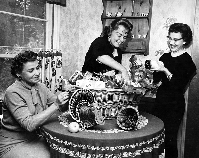 "Photograph caption dated November 21, 1962 reads, ""Members of Xi Eta Zeta Chapter of Beta Sigma Phi, from left, Mmes. Robert Nelson, North Hollywood; Al Austin, Van Nuys, and Arthur True, also North Hollywood, prepare Thanksgiving basket for group's adopted needy family. They have been aiding the same Pacoima family at Thanksgiving and Christmas for the past three years. Other projects include making clowns and rag dolls for the children's ward at General Hospital."""