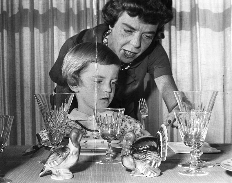 "Photograph caption dated November 19, 1962 reads, ""Little Laurie, 4 1/2, learns everything about Thanksgiving from setting the table to its meaning."""