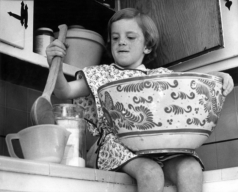 "Photograph caption dated November 19, 1962 reads, ""Laurie helps mother prepare huge dish for dinner guests."""