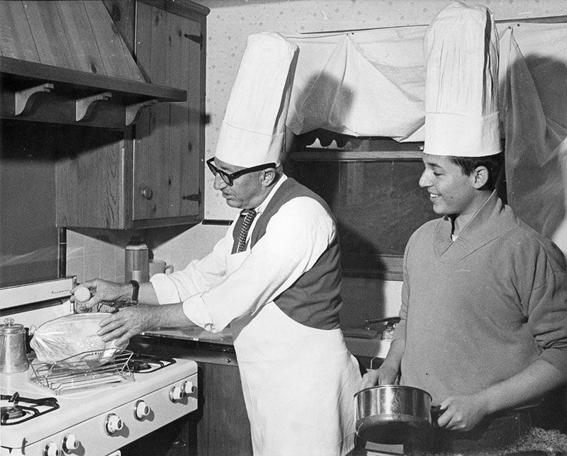"Photograph caption dated December 21, 1964 reads, ""John Cassidy and son, Cass, share cooking chores in Chatsworth home."""