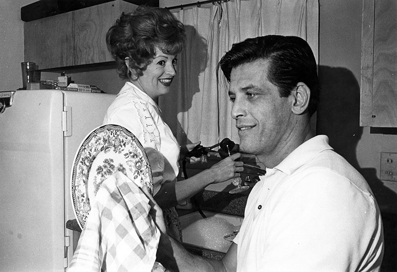 Photograph dated November 18, 1961 shows actor Gerald Lazarre helping his wife, actress Julie North, with the dishes in preparation for Thanksgiving dinner at their home in North Hollywood.