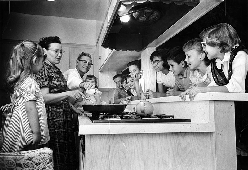 """Photograph caption dated November 23, 1961 reads """"From left, Eva, Mrs. Sawlsville, Sawlsville, Leslie, Dennis, Sandy, Terry, David, Cynthia, Leonard, Diana, Sharon."""" The family, in Sepulveda, grew when the Sawlsvilles adopted their seven grandchildren after the deaths of the children's parents. The Sawlsvilles also had three children of their own still living at home."""