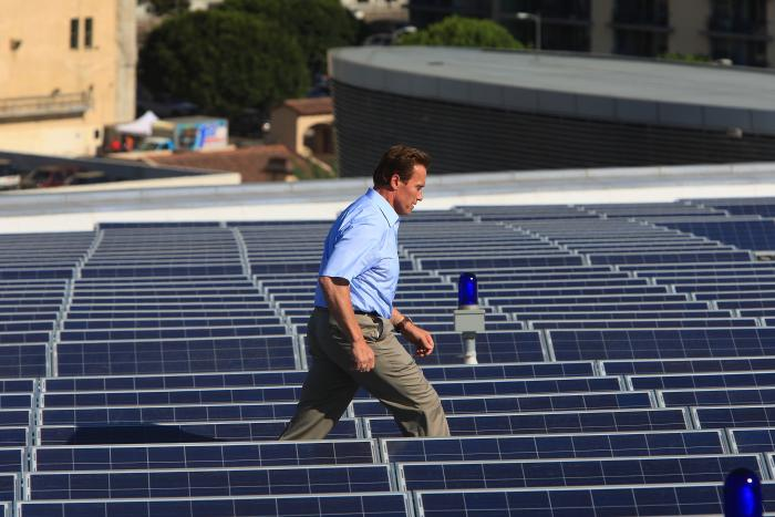 California Gov. Arnold Schwarzenegger walks amid solar panels after attending a news conference for the installation the last of 1,727 solar panels on the rooftop of the Staples Center sports complex on October 28, 2008 in Los Angeles, California. The off-grid 345 kilowatt photovoltaic solar system, which covers 24,196 square feet, will provide power to Staples Center and the new Nokia Theatre L.A. Live sports and entertainment venues. (Photo by David McNew/Getty Images)