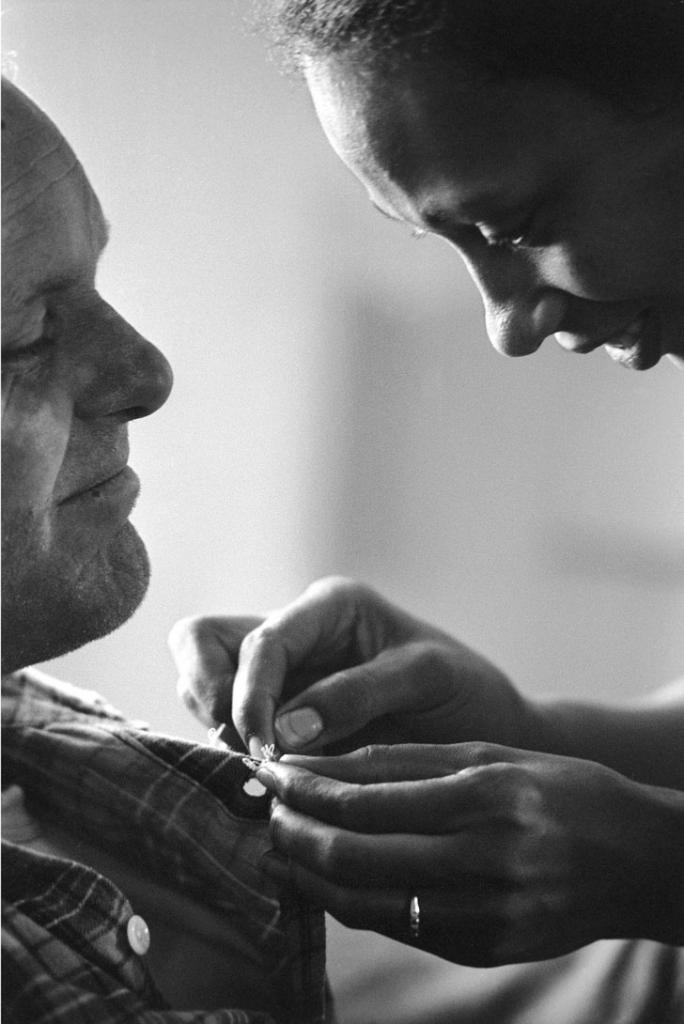 Mildred sews a button on Richard's shirt, King and Queen County, Virginia, 1965