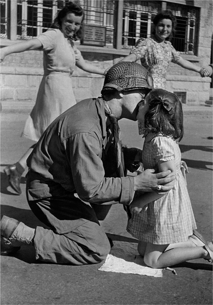 """Kiss of Liberation"" Sergeant Gene Costanzo kneels to kiss a little girl during spontaneous celebrations in the main square of the town of St. Briac, France, August 14, 1944"