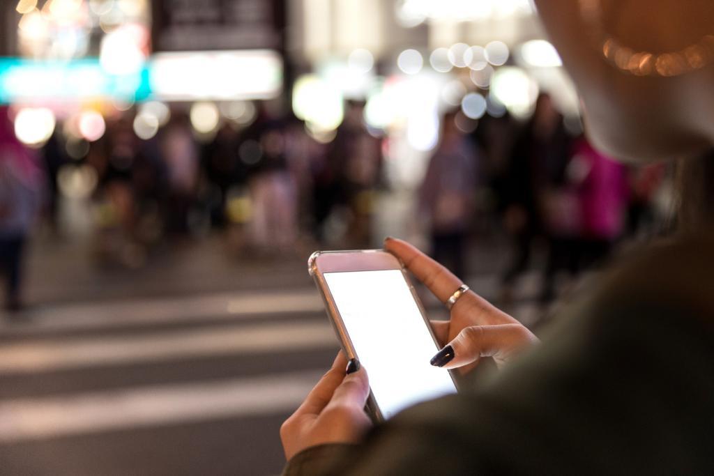 female hands uber app phone street