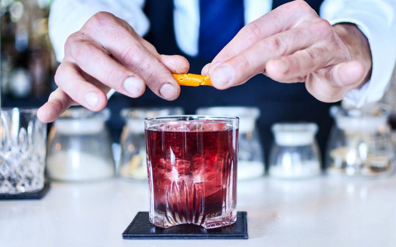bartender makes a negroni cocktail negroni week campari