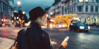 woman waiting for uber rideshare app phone street